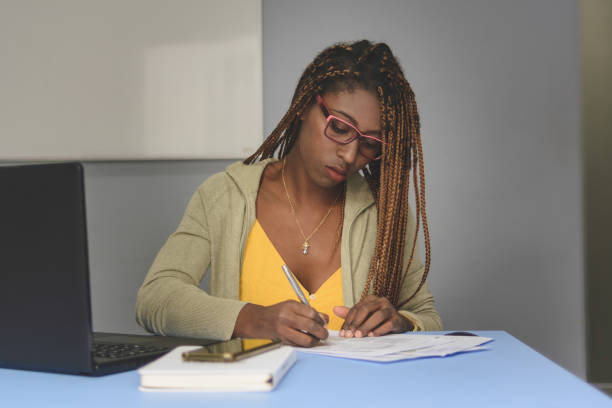 Young business woman working with laptop making notes or filling forms stock photo