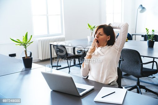istock Young business woman yawning at a modern office desk in front of laptop. 697249000