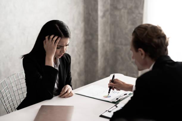 Las jóvenes mujeres de negocios con traje negro están estresadas. Las quejas de los jefes en el escritorio de la oficina funcionan en tono oscuro. Estrés empresarial y concepto de problema laboral. - foto de stock