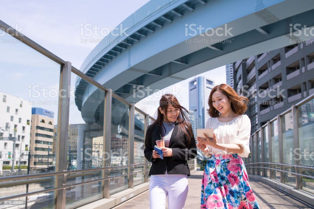 Young business women walking together and watching screen on digital tablet stock photo