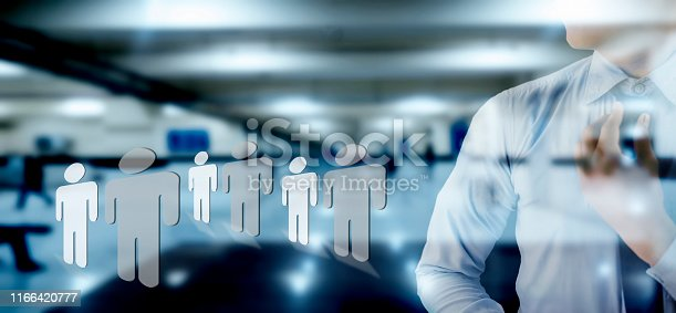 635949862 istock photo Young businessman adjusting his black colored necktie with a blurred background of office with some human shape icons on the floor concept of opportunities and employment. 1166420777