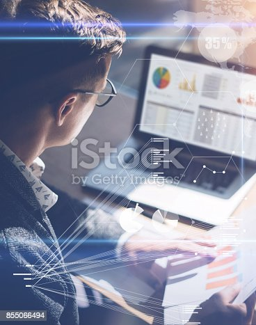 474953508 istock photo Young businessman analyze stock report on notebook screen.Concept of digital screen,virtual connection icon,diagram,graph interfaces on background.Vertical. 855066494