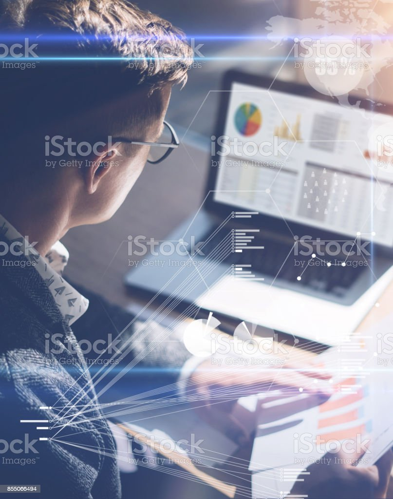 Young businessman analyze stock report on notebook screen.Concept of digital screen,virtual connection icon,diagram,graph interfaces on background.Vertical. stock photo