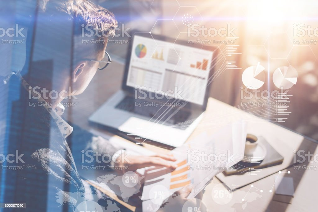 Young businessman analyze stock report on notebook screen.Concept of digital screen,virtual connection icon,diagram,graph interfaces on background.Double exposure. stock photo