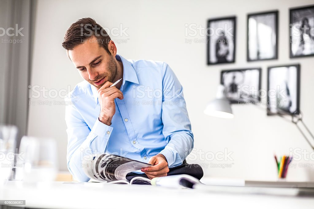 Young businessman analyzing brochure at desk in office – Foto