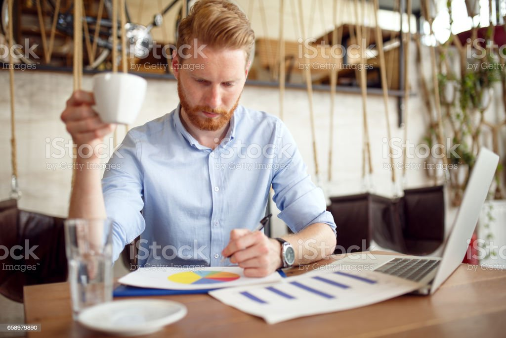 Young businessman analyzing graphs during coffee break. royalty-free stock photo