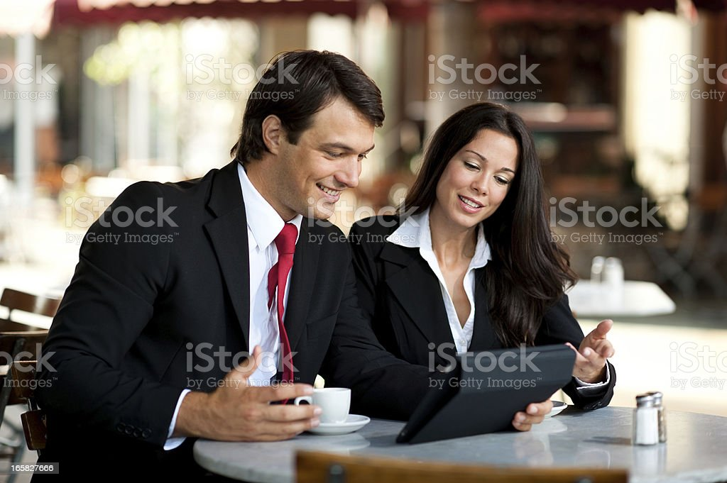 Young Businessman and Businesswoman Discussing Digital Tablet iPad royalty-free stock photo