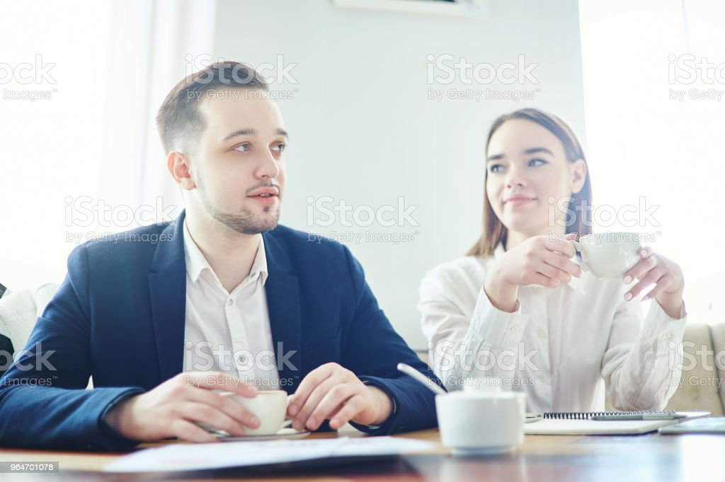 Young businessman and businesswoman drinking coffee and talking. Business collegues having friendly meeting at cafe royalty-free stock photo