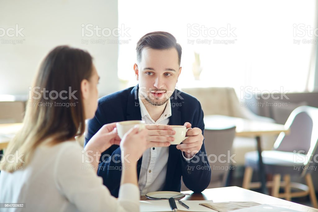 Young businessman and businesswoman having coffee in cafe and discussing work, focus on man royalty-free stock photo