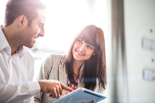 Young Businessman And Businesswoman Using Digital Tablet In Office - 2人のストックフォトや画像を多数ご用意
