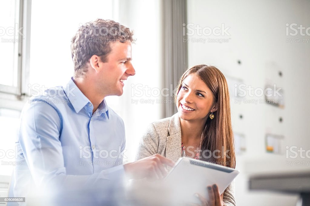 Young businessman and businesswoman using digital tablet in office stock photo