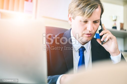913346608 istock photo Young businessman are busy working in the office. He using mobile and talking about his business with partner company 1209869223