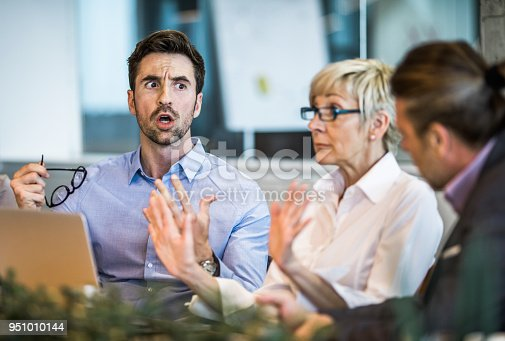 istock Young businessman arguing with his colleague on a meeting in the office. 951010144