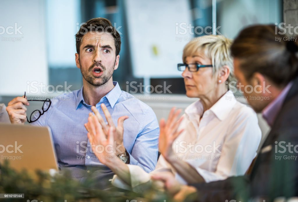 Young businessman arguing with his colleague on a meeting in the office. stock photo