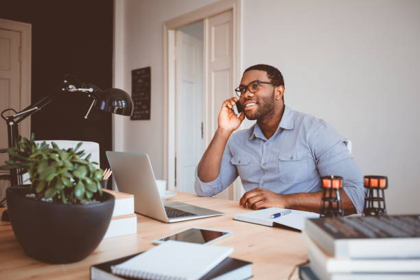 Young businessman at home office talking on phone stock photo