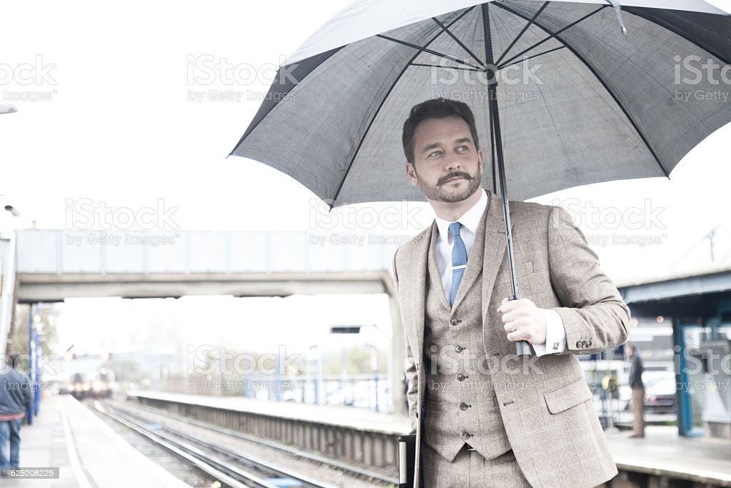 Young Businessman at the Train Station Carrying an Umbrella stock photo