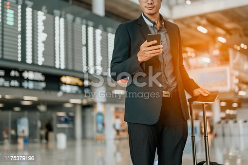 Young businessman at timetable screen board using smart phone.Flight board.