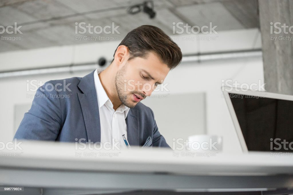 Young businessman at work Young businessman sitting at table and working. Caucasian male executive working in office. 25-29 Years Stock Photo