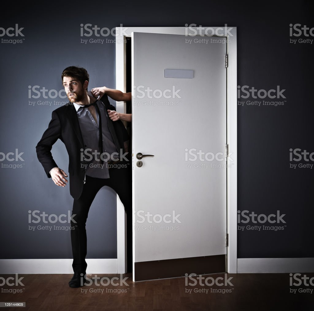 Young businessman being pulled back to office royalty-free stock photo