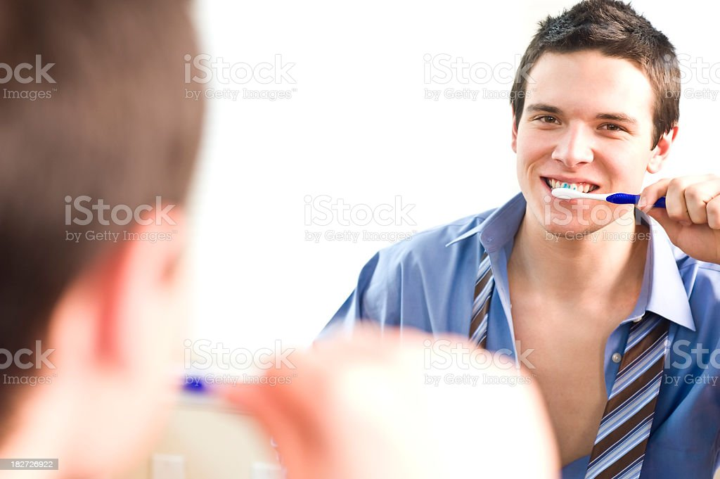 Young businessman brushing teeth while getting ready for work stock photo