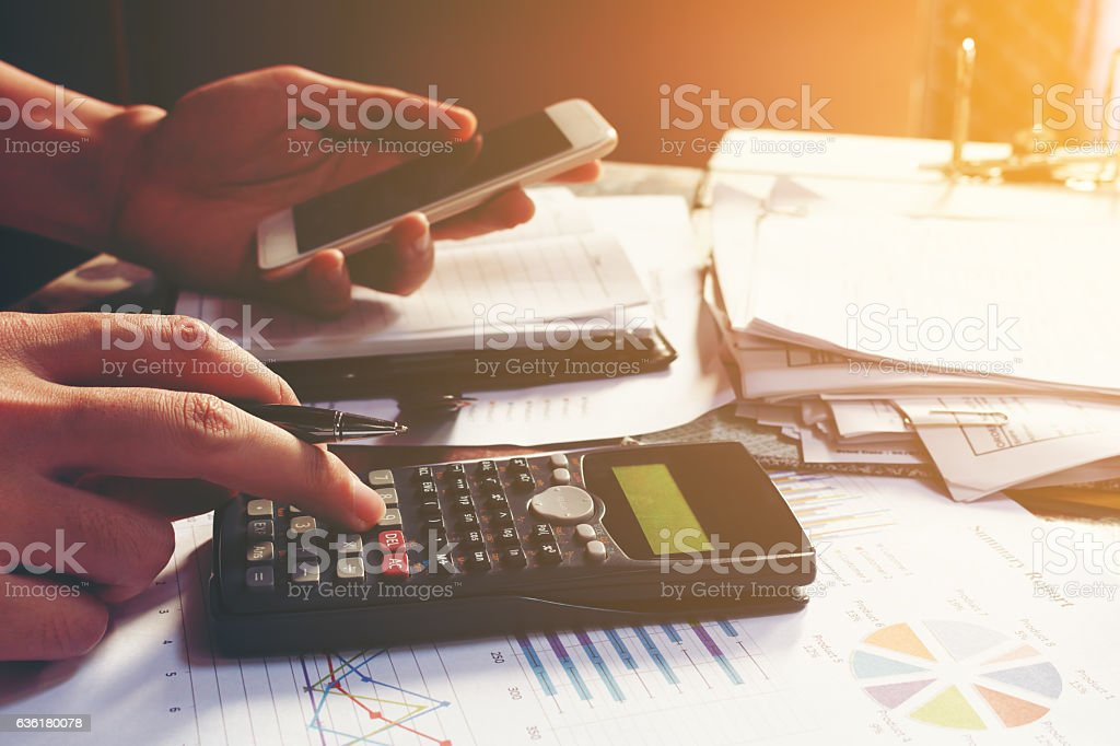 Young businessman calculating about cost and using smartphone se stock photo