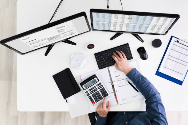 Young Businessman Calculating Bill In Office stock photo