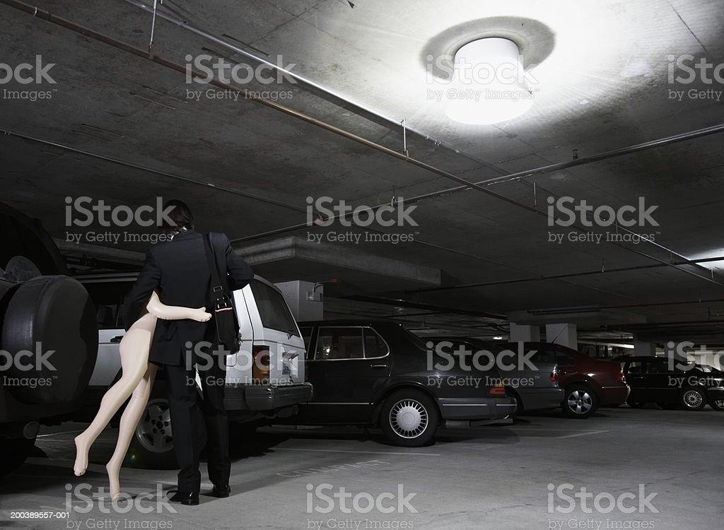Junger Geschäftsmann, tragen Aufblaspuppe in der Parkgarage, hinten – Foto