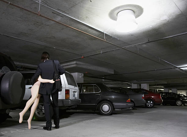Young businessman carrying blow-up doll in parking garage, rear view  sex toy stock pictures, royalty-free photos & images