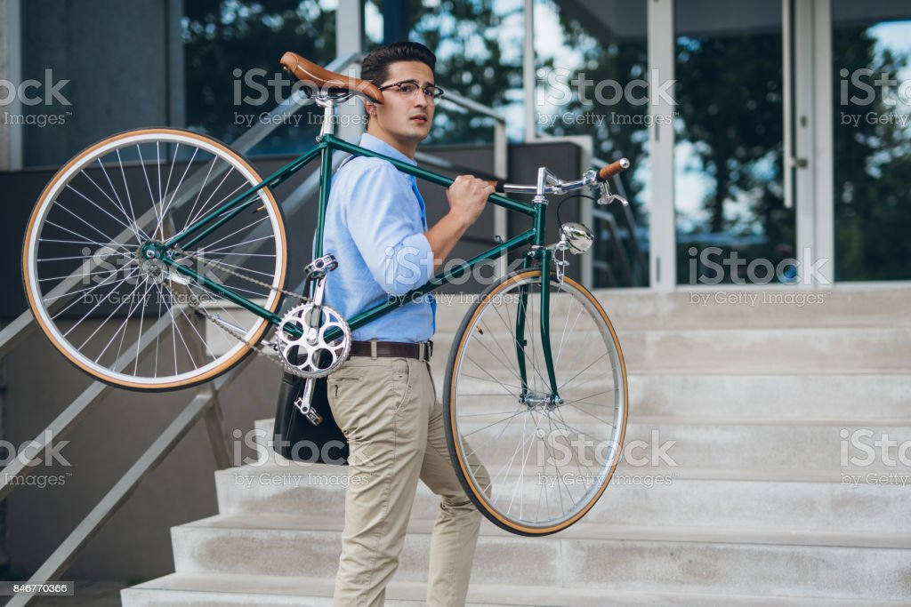 Young businessman carying his bicycle up stairs stock photo