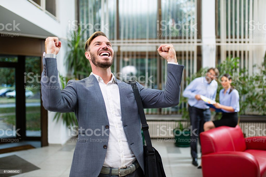 Young businessman celebrating success with arms raised. stock photo