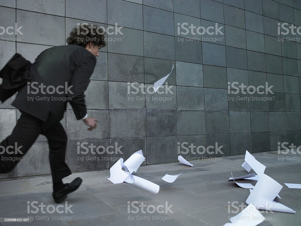 Young businessman chasing pieces of paper blowing in wind, rear view stock photo