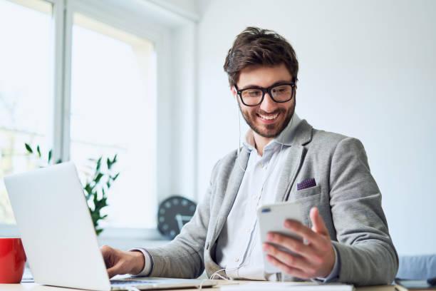Jungunternehmer, der während der Arbeit im Home Office telefoniert – Foto