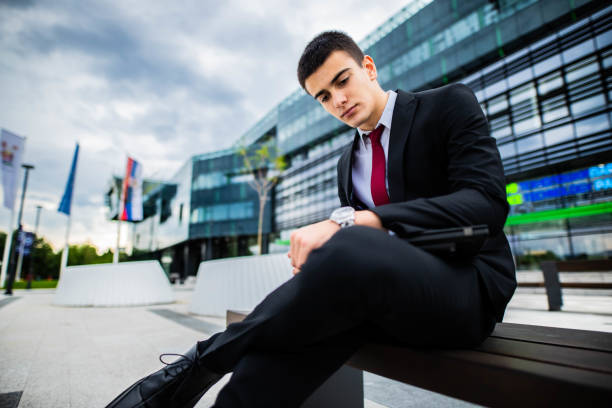 Young businessman checking the time on  watch