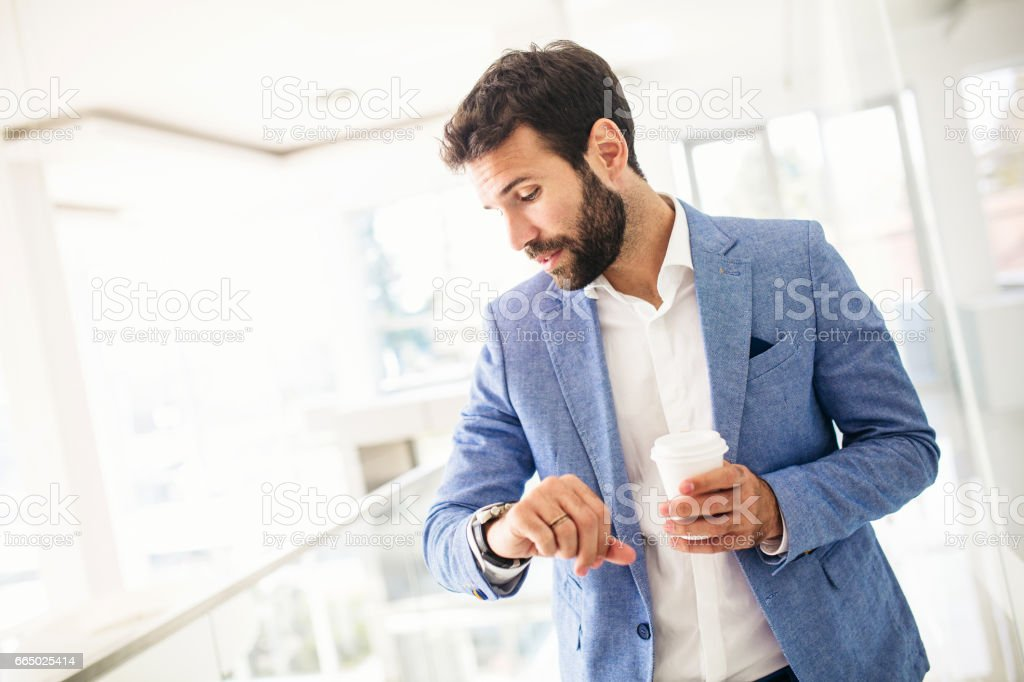 Young businessman checking the time stock photo