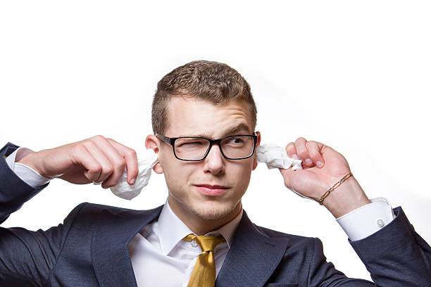 young businessman cleaning his ears with a cotton tissue - cursed stock pictures, royalty-free photos & images