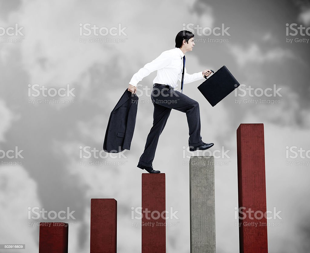 Young businessman climbing grey and red steps stock photo