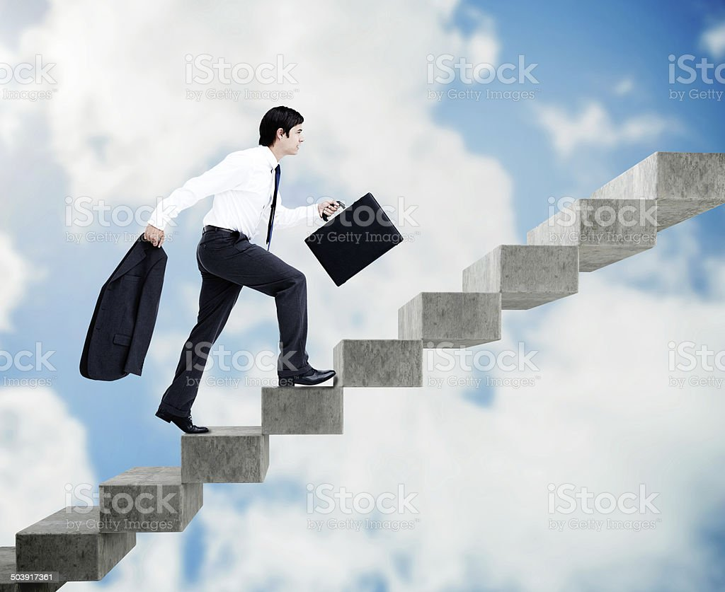 Young businessman climbing grey stairs stock photo