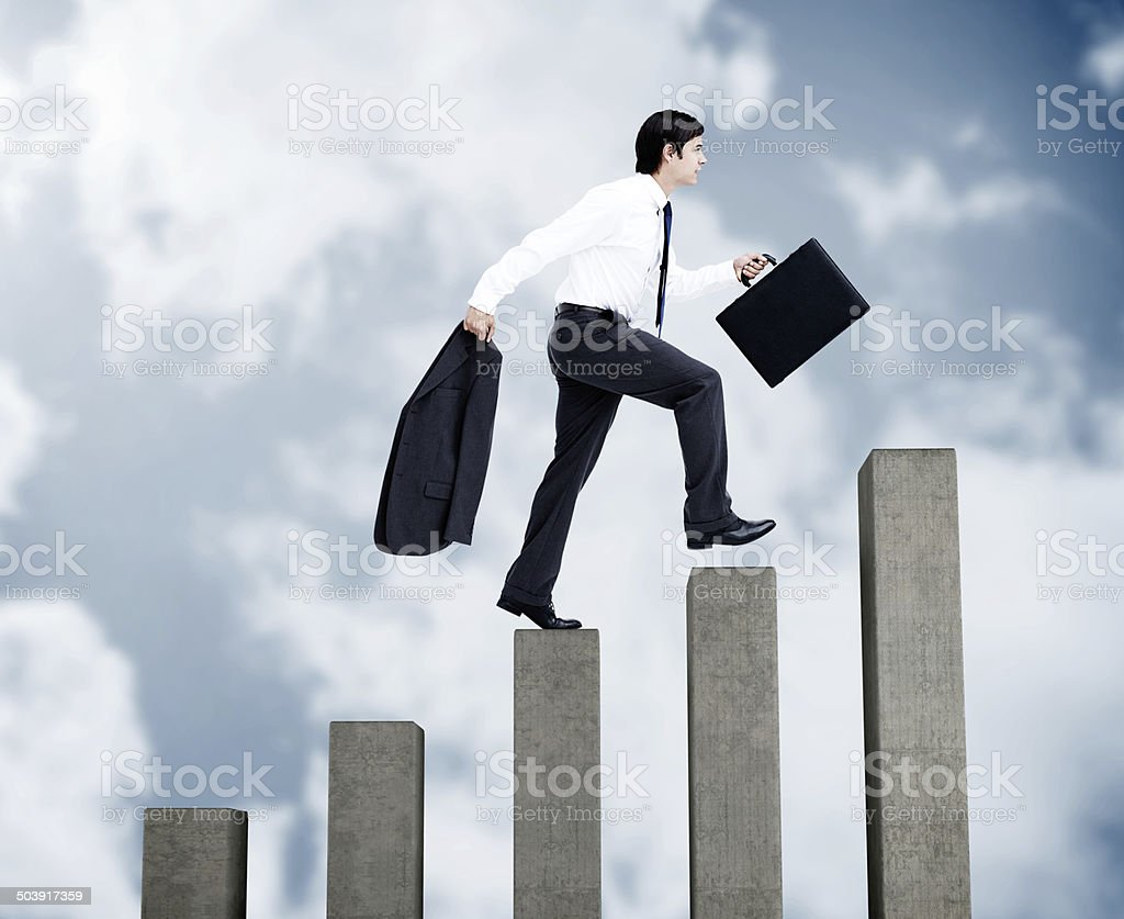 Young businessman climbing grey steps stock photo