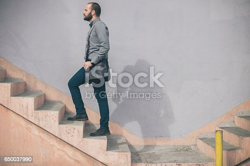 istock Young businessman climbing stairs 650037990