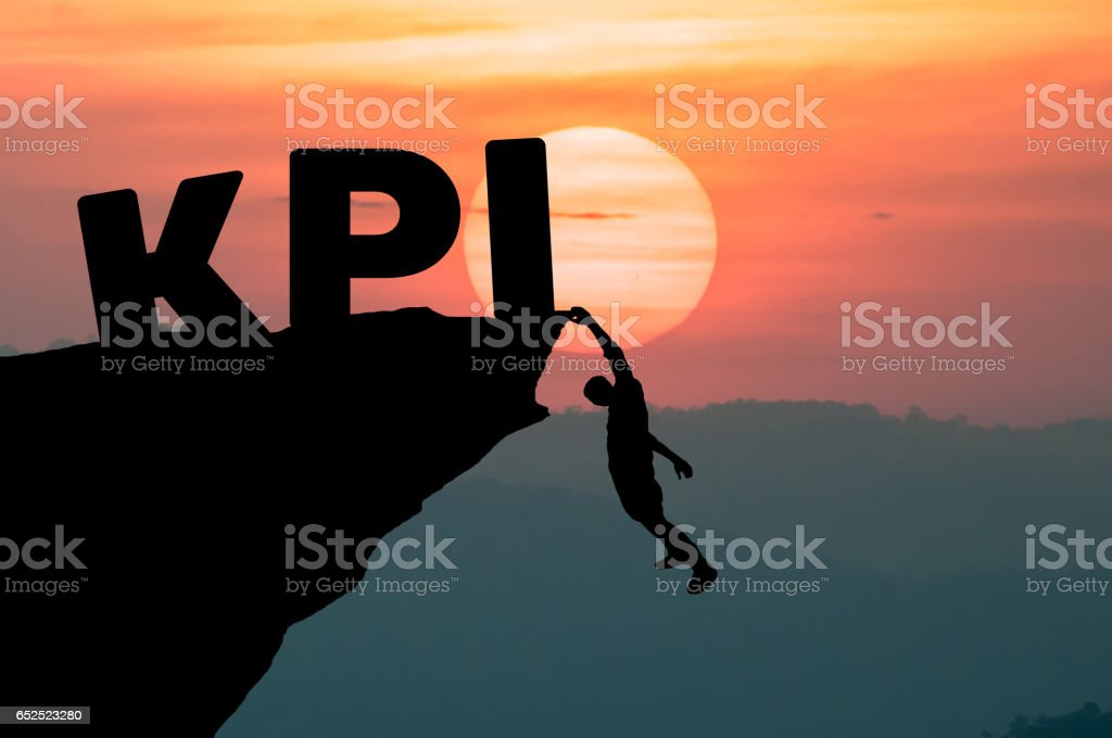 Young businessman climbing the mountain to achieve KPI with sunset background. (to reach key performance indicator) stock photo