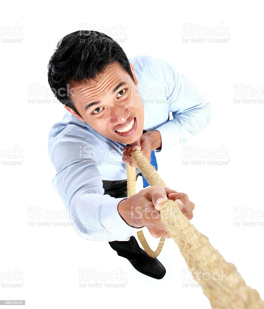 Young businessman climbing up by using a rope stock photo