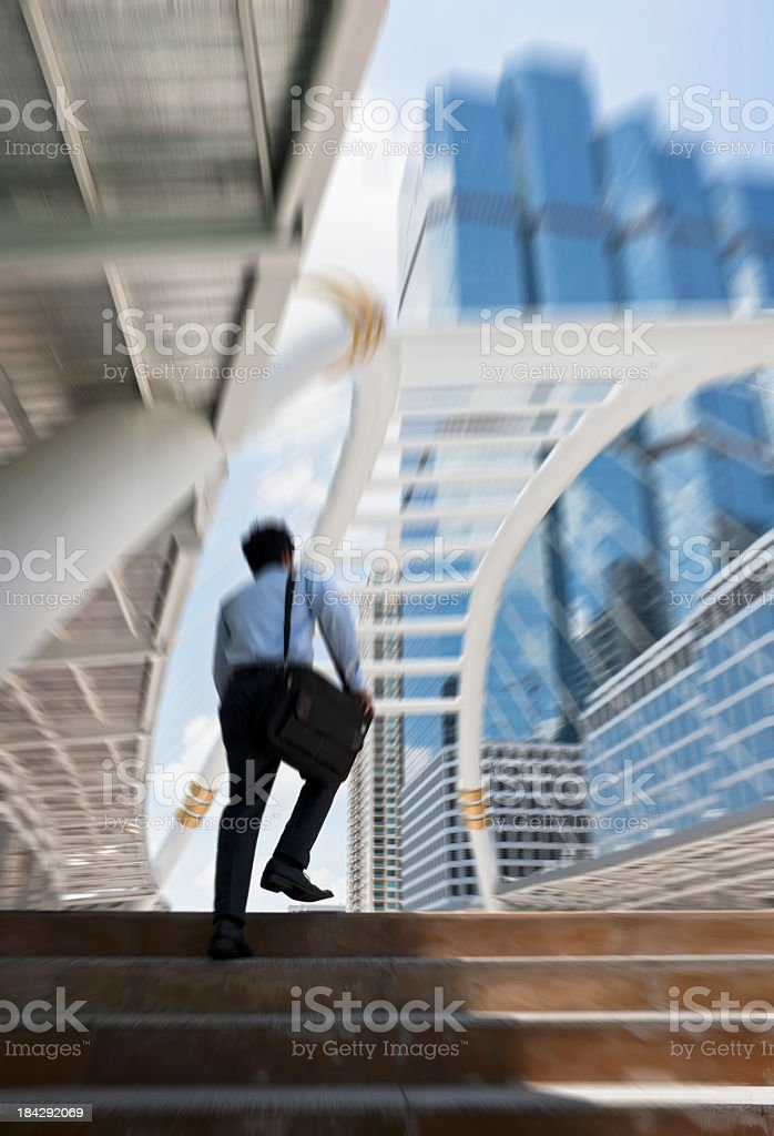 Young businessman climbs steps towards the city. royalty-free stock photo