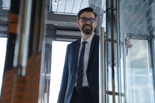 Young businessman coming in the hotel in a good mood stock photo