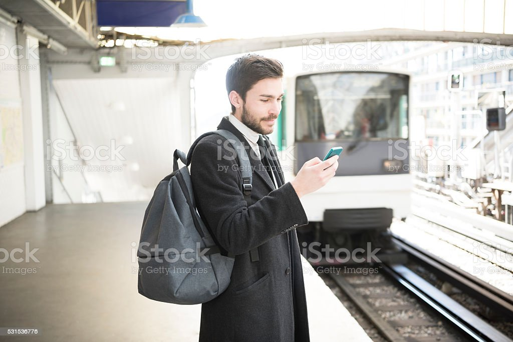 Young businessman commuter using smartphone transport app stock photo