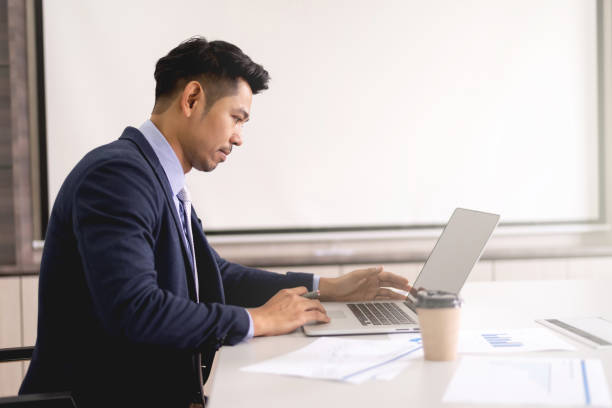 Young businessman concentrate working on laptop with white screen background stock photo