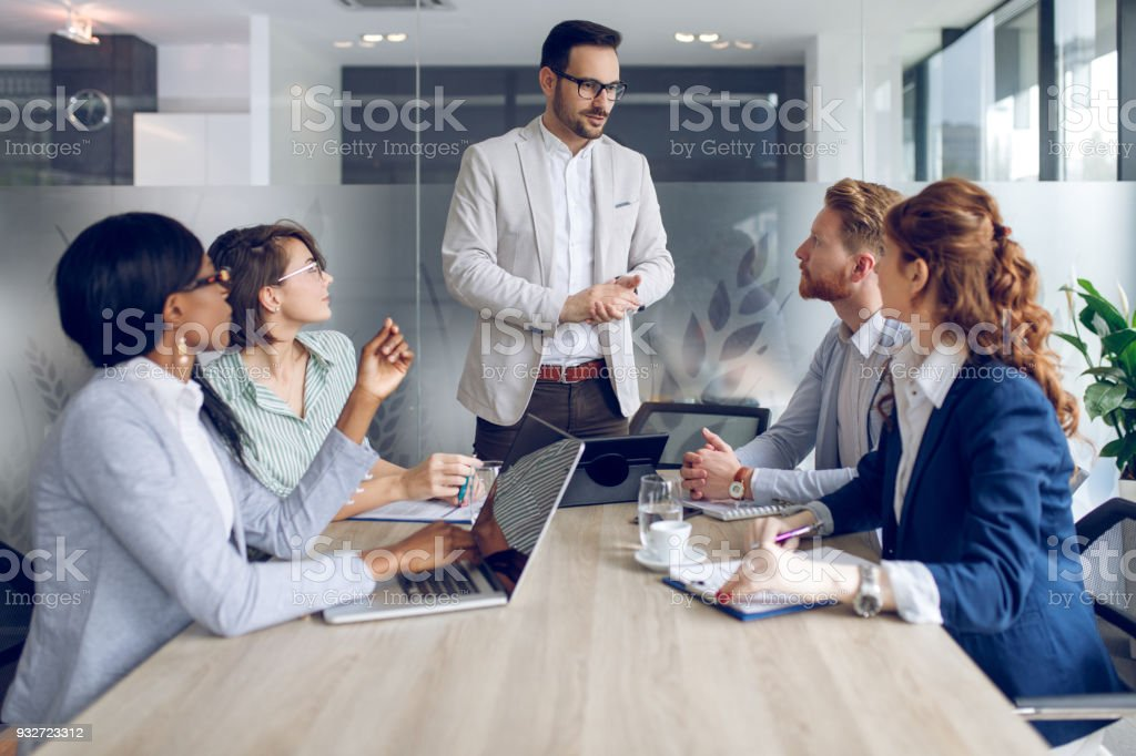 Young businessman discussing sale analysis with colleagues stock photo