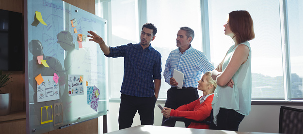 istock Young businessman discussing with colleagues at office 824580648