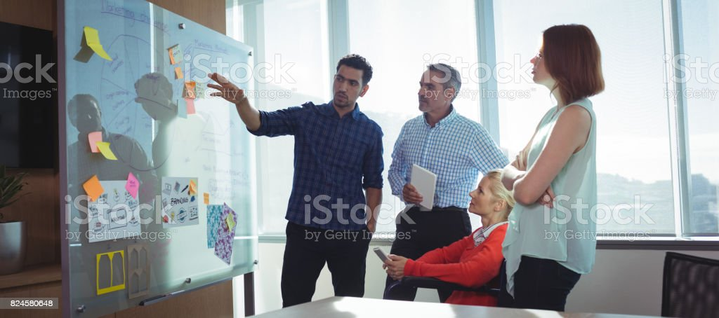 Young businessman discussing with colleagues at office stock photo