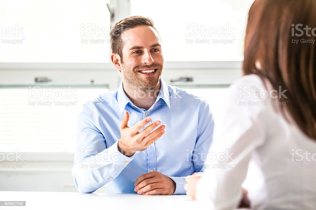Young businessman discussing with female colleague in office stock photo