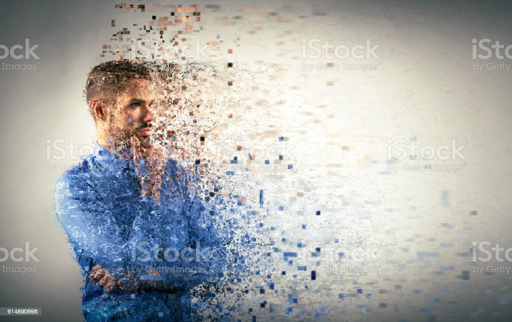 Young businessman dispersing into pixels. stock photo